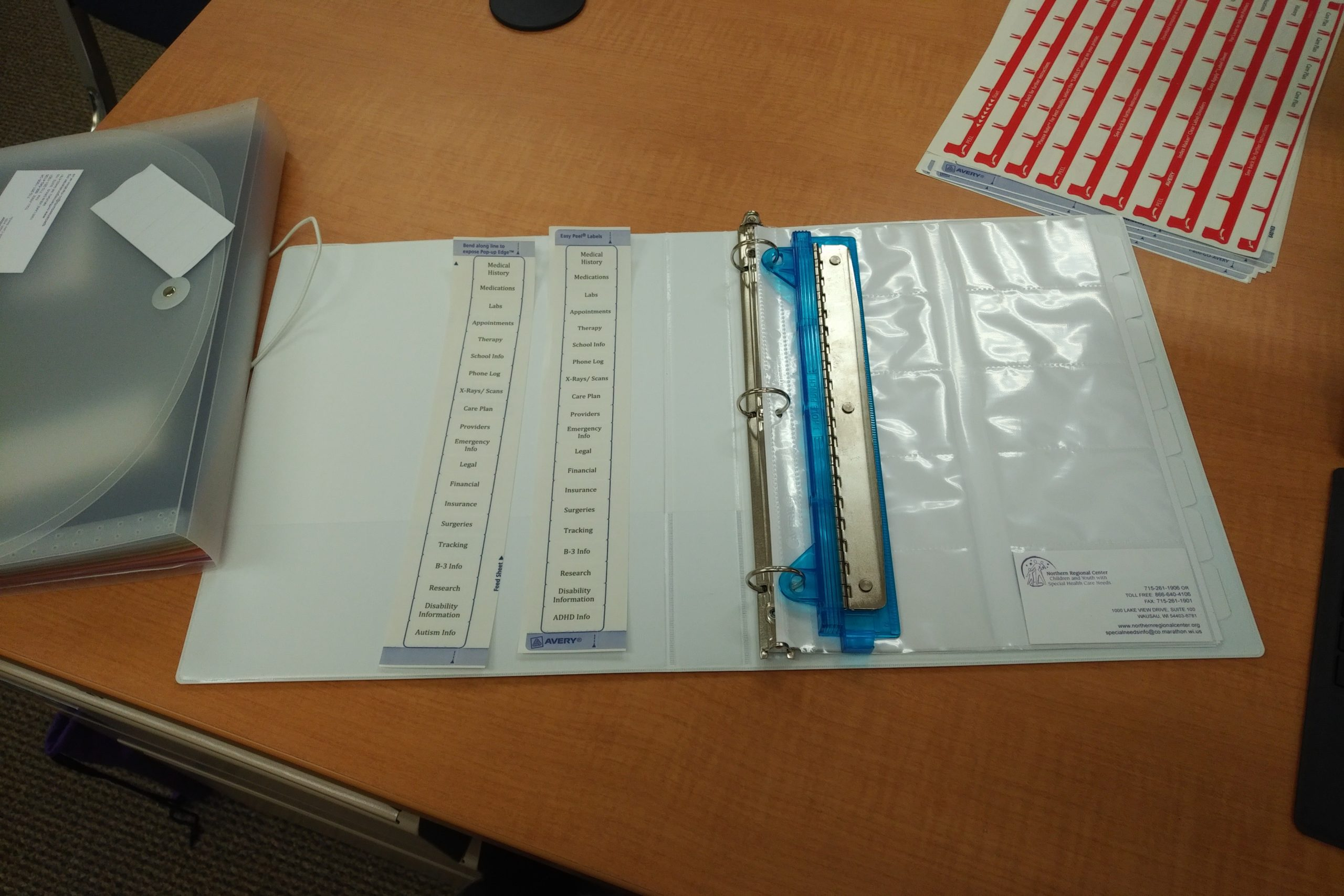 Picture of notebook with labels and hole punch